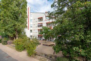 Inakindergarten, Raumfotos, Kita Grüntaler Strasse, Außenansicht Kitagebäude mit Bäumen